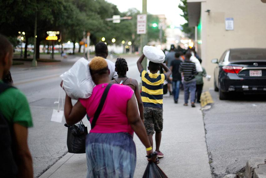 A group of migrants mostly from Africa walk a few blocks on June 26, 2019 from a makeshift processing center in downtown S...