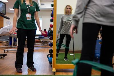 Flo Rice works out her legs by using resistance bands in a balance and hip strengthening exercise. Having been shot in both legs, Rice attends therapy 3-4 times a week to improve strength and stability.