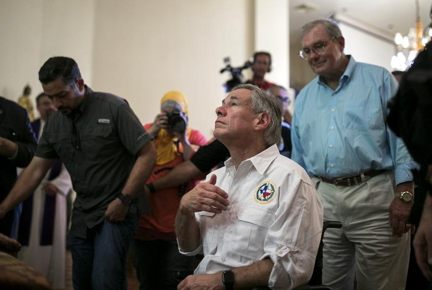 Texas GOP Gov. Greg Abbott prays after a vigil at a Catholic church as El Paso Mayor Dee Margo stands in the back, Saturda...