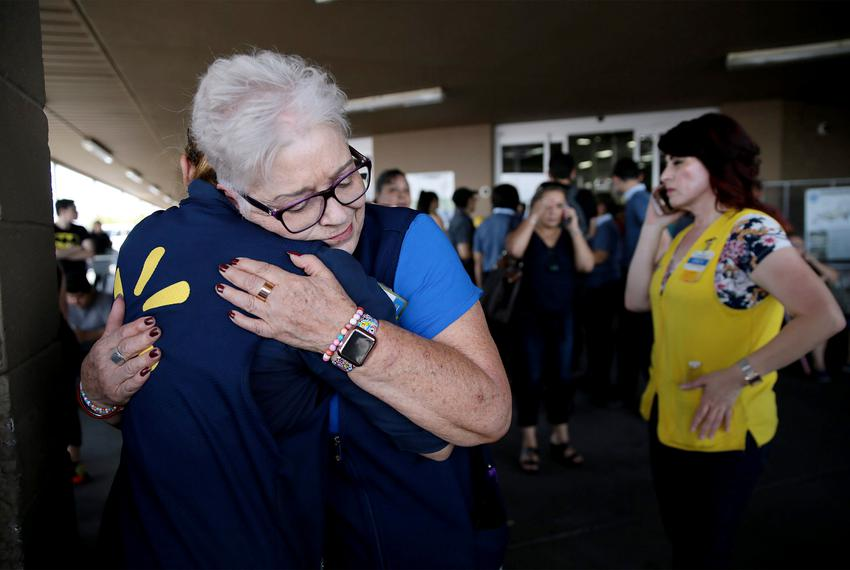 WalMart employees comfort one another after an active shooter opened fire at the WalMart at Cielo Vista Mall in El Paso Sa...