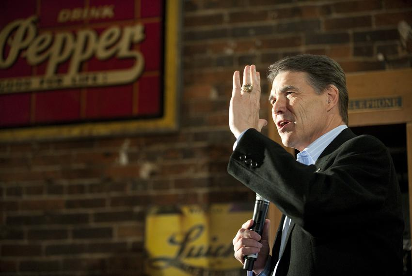 Rick Perry stands in the spotlight while answering a question at the Smokey Row Coffee House in Oskaloosa, Iowa on December …