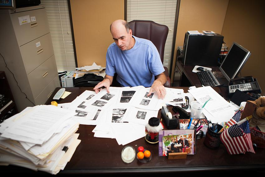 Victim Advocate for the City of Houston Andy Kahan, with crime scene photos printed off websites showing dead bodies, many u…