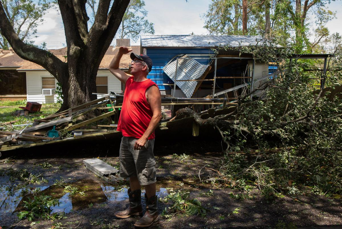 Drainage foreman Robert Walker scans the side of his house for storm damage after Hurricane Laura blew through Orange.