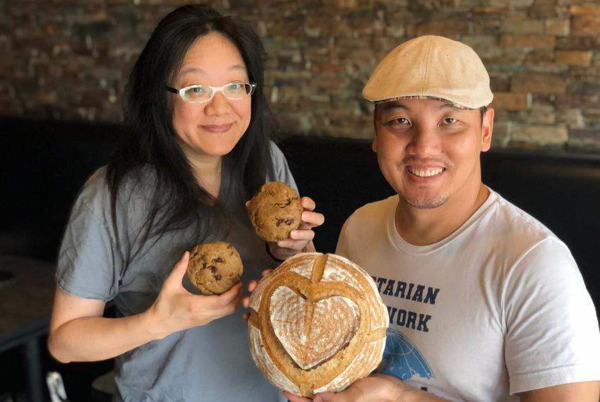 Debbie Chen and Nguyen T. Nguyen, a local artist and photographer, hold Sourdough bread and chocolate filled cookies