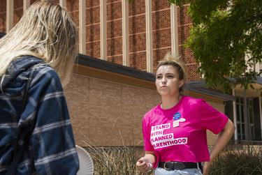 Sofia Bell talks with a potential voter about voting against Proposition A on the Texas Tech University campus on May 1, 2021, in Lubbock.
