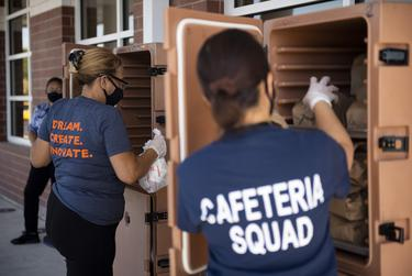 Round Rock ISD food service workers Tania Hernandez and La Vuong prepare meals to distribute to families during a curbside meal distribution at Joe Lee Johnson Elementary School in Round Rock.