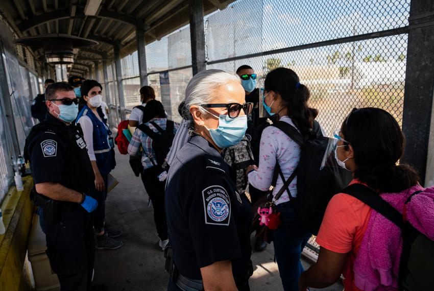 Asylum seekers wearing face shields make their way to be processed in the U.S. at the Gateway International Bridge in Matamo…