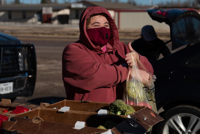 Marfa resident Ellie Tejada gathers produce from the Marfa Food Pantry Saturday morning. Tejada didn't have power at her hou…