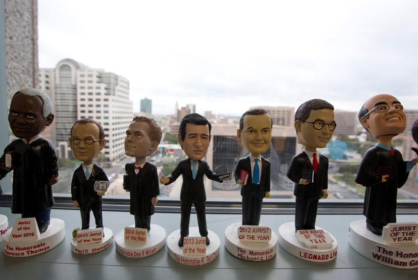 A collection of bobblehead figurines in the likenesses of judges who have won the Jurist of the Year award, inside the off...