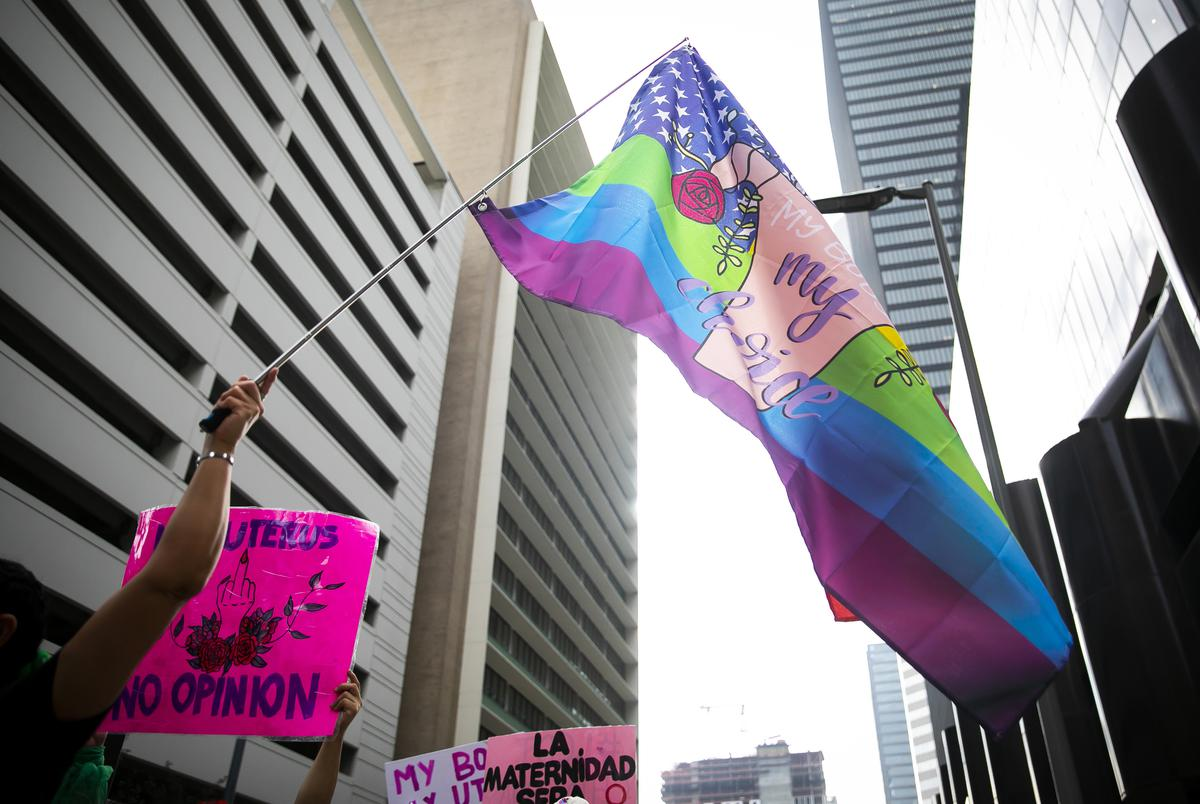 A participant waves a flag during the 2021 Women's March on Texas in downtown Houston on Saturday, Oct. 2, 2021.