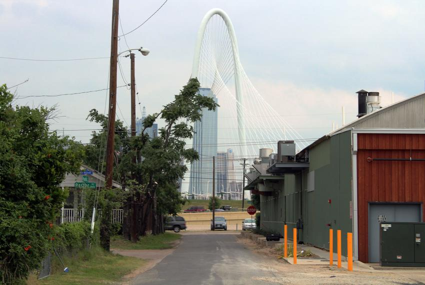 The Margaret Hunt Hill Bridge, which opened in 2012, looms over West Dallas where a street divides the new Trinity Groves cl…