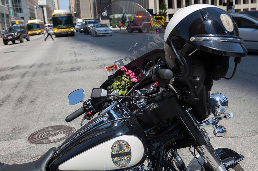 Flowers sit on the dash of a Dallas Area Rapid Transit police motorcycle as it is used to block off the scene where, the night before, snipers targeted police officers, killing five, after a peaceful Black Lives Matter protest in downtown.