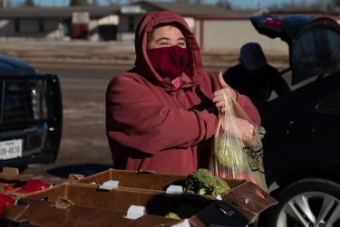 Marfa resident Ellie Tejada gathers produce from the Marfa Food Pantry Saturday morning. Tejada didn't have power at her house for three days this week and had to throw out her food.