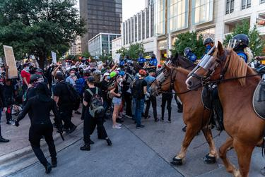 Mounted officers from the Austin Police Department clash with protesters on the corner of Fourth St. and Congress Ave. in downtown Austin on Aug. 1, 2020.