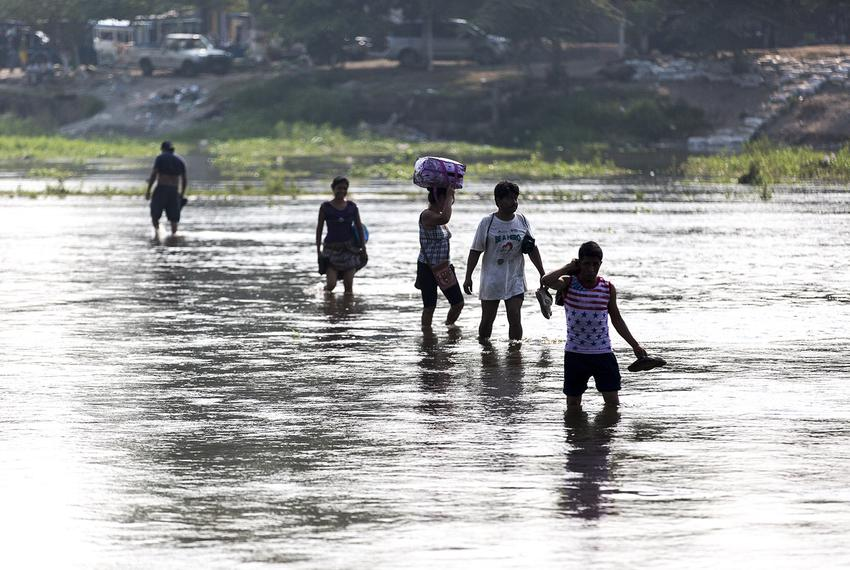 People wade across the Suchiate River separating Ciudad Hidalgo, Mexico, and Tecun Uman, Guatemala, carrying their shoes, cl…
