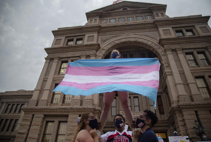 Ali Cross of the Austin Cheer squad waves a trans flag while her squad mates hold her up on the steps of the state Capitol a…