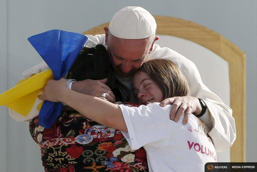 Pope Francis hugs two girls during a meeting with youths at José María Morelos y Pavón stadium in Morelia, Mexico on Feb. ...