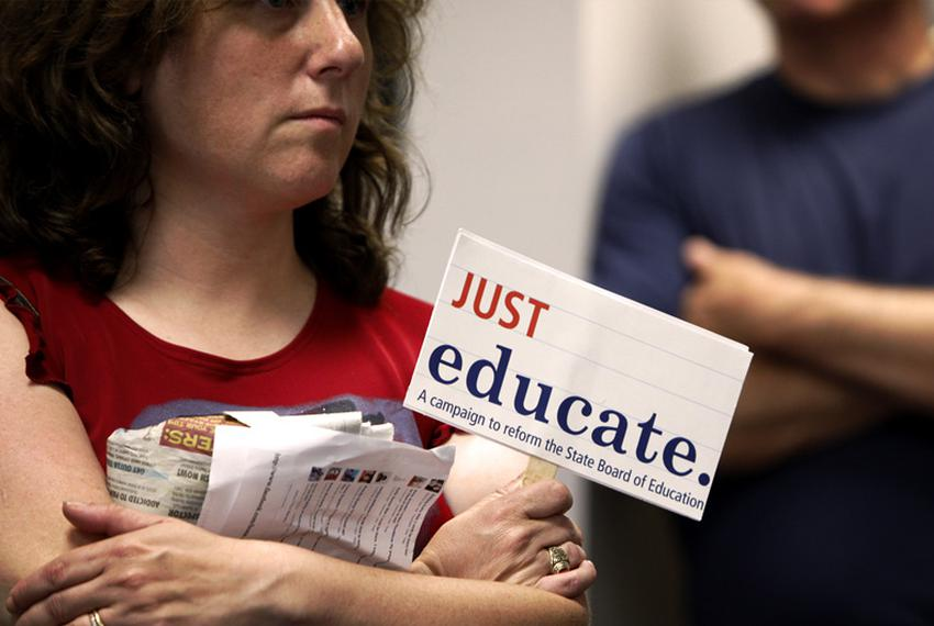 An observer holds a protest sign during testimony at the State Board of Education (SBOE) textbook hearings on Wednesday, M...
