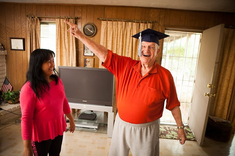 Robert Titus tries on his graduation cap with the help of his wife, Jennifer, in his Houston home on Nov. 26, 2012. Titus recently earned an online degree in marketing managment from WGU Texas.