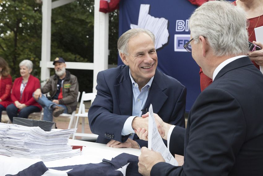 Gov. Greg Abbott and Republican Party of Texas Chairman James Dickey shake hands after Abbott formally filed his papers for re-election, on Saturday, Nov. 11, 2017 in Austin.