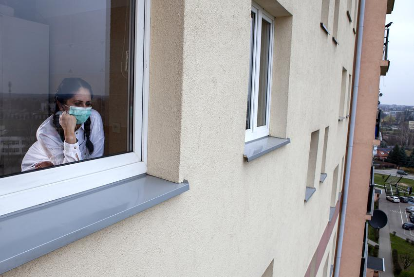 A woman wearing a protective mask looks out of a window during the COVID-19 pandemic.