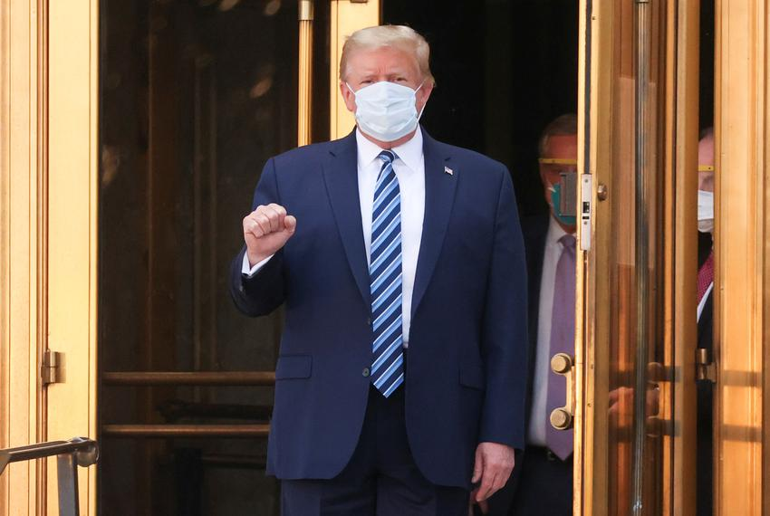 President Donald Trump makes a fist as he walks out the front doors of Walter Reed National Military Medical Center after a …