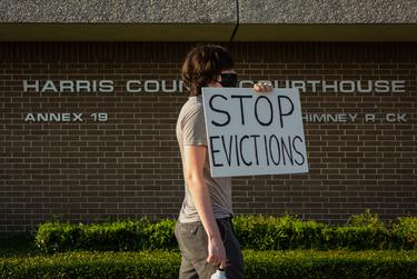 """A protester holds up a """"stop evictions"""" sign outside the Harris County Courthouse in Houston on Aug. 21, 2020."""