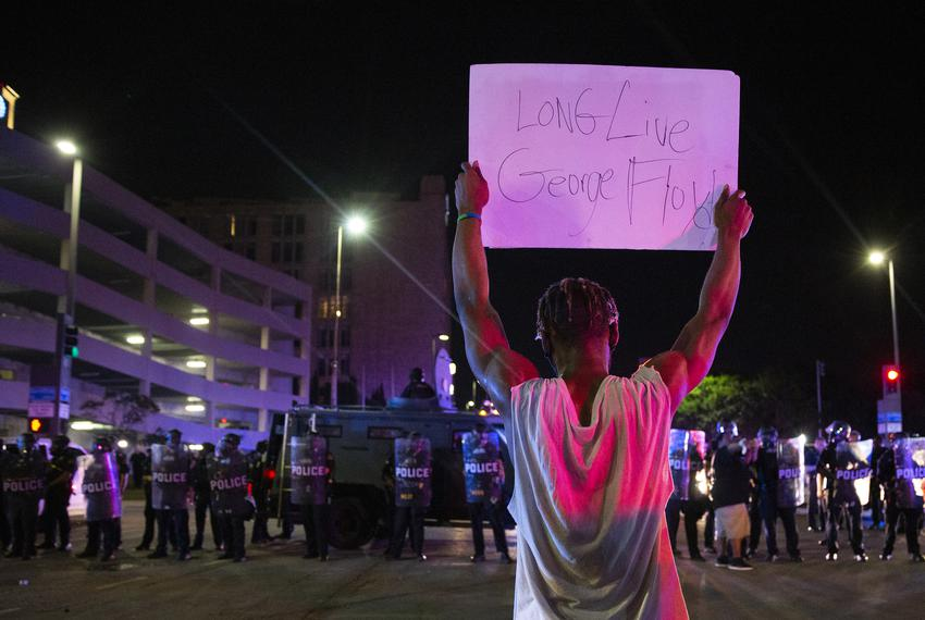 A protester holds a sign towards a line of Dallas police at a march and rally for George Floyd in Dallas on May 29, 2020.