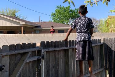 Maxwell Norman, 9, talks to a neighbor over his family's back fence in Midland.
