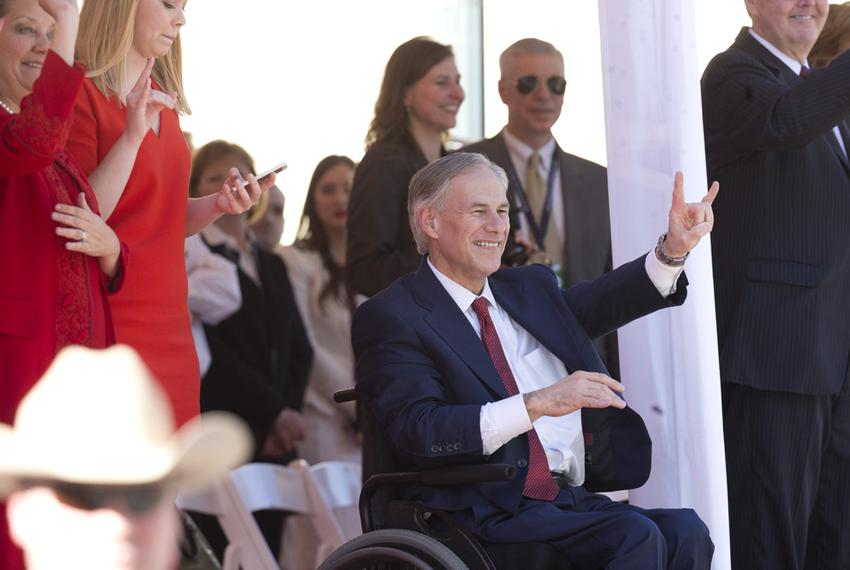 Abbott shows his allegiance to the University of Texas as the Longhorn Band passes by in the inaugural parade.