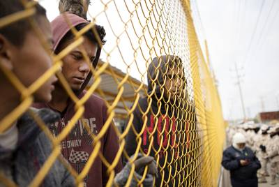 From left, Elmer de la Rosa, Orlando Jose Reyes and Carlos Lanza stand near the perimeter of the migrant shelter in Piedras Negras, Coahuila, on Feb. 9, 2019.