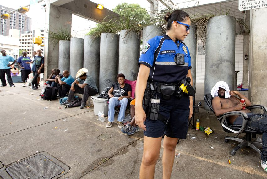 APD officers speak to people gathered on sidewalk in front of the Austin Resource Center for the Homeless, or ARCH, in downtown Austin on Aug. 4, 2019