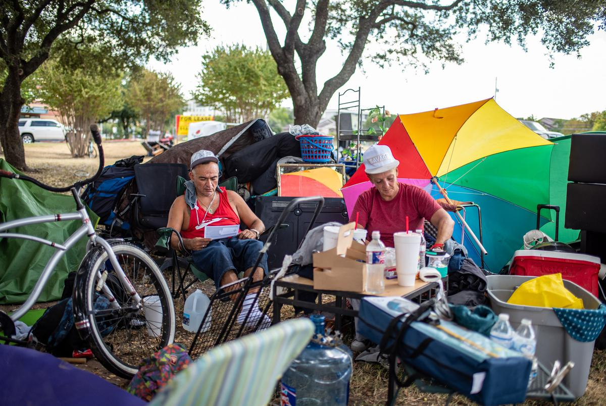 Adrian Elliot and Shirley Crawford sit near a former homeless encampment oN Riverside Drive on Sept. 28, 2021 in Austin. Many of the people who had been living in the camp said they weren't given enough notice and were not offered any place to stay.
