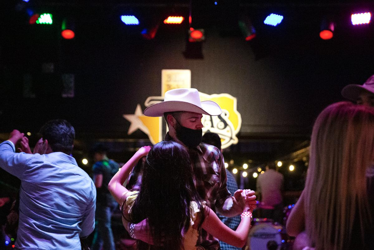 Guests dance at Billy Bob's Texas, a honky-tonk in Fort Worth. Billy Bobís has been operating since August 13 under food and beverage guidelines after previously being classified as a bar. Bars that did not already get the food and beverage license were allowed to reopen October 14 at 50% capacity, and must stop selling alcohol by 11 pm.