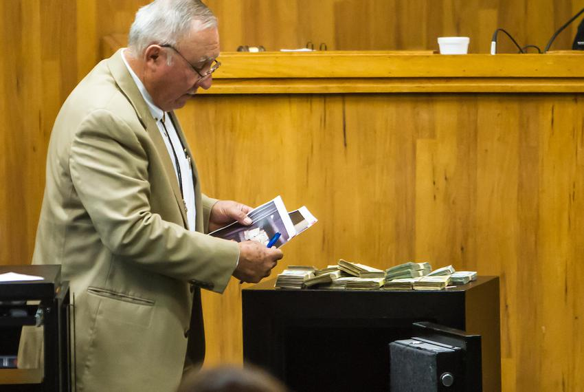 Chief Prosecutor Gus Garza examines a safe and cash seized from Border Patrol Agent Joel Luna's mother-in-law's home durin...