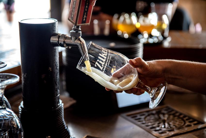 A bartender pours a beer behind the bar at Zilker Brewery in Austin.
