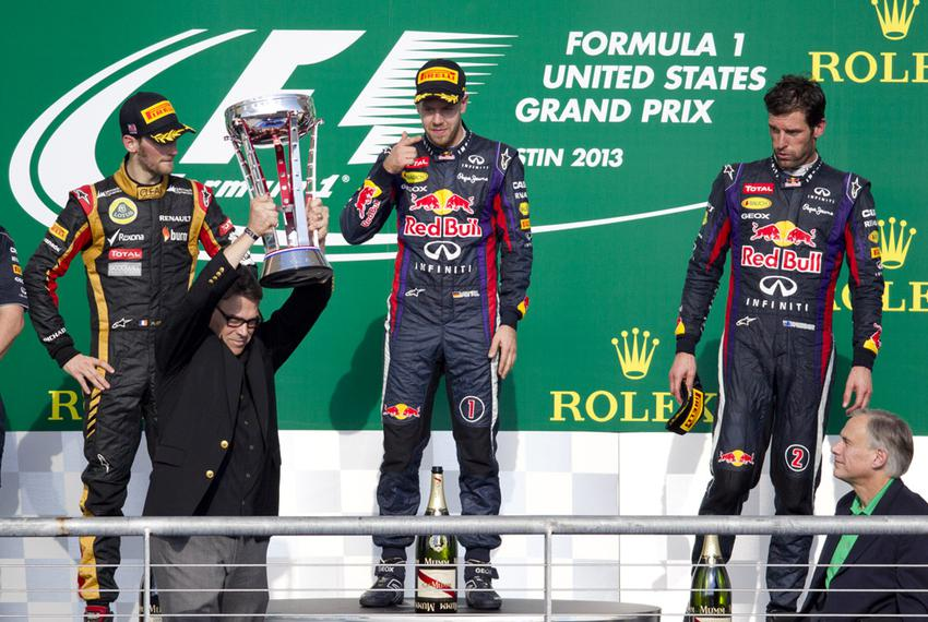 Then-Gov. Rick Perry hoists the Formula One U.S. Grand Prix trophy on November 17, 2013, with Attorney General Greg Abbott w…