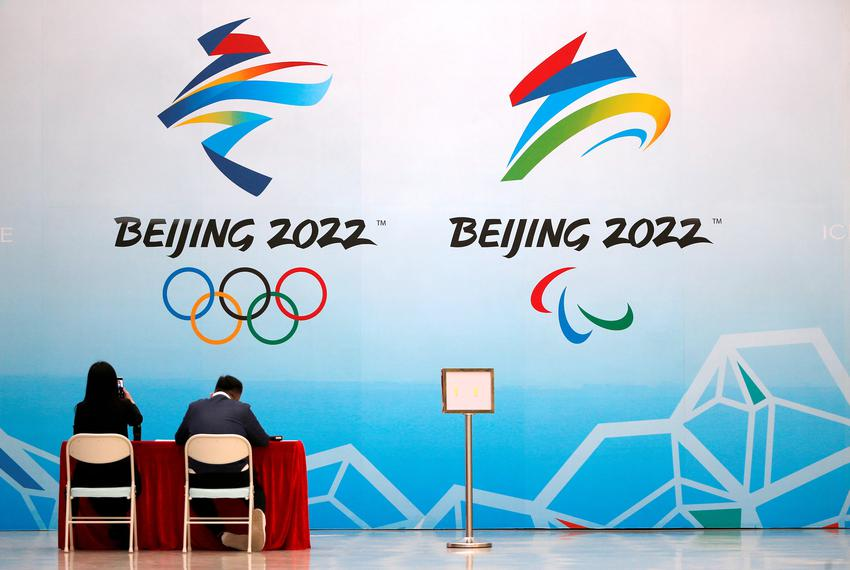 Staff members sit near a board with signs of the 2022 Olympic Winter Games, at the National Aquatics Center in Beijing, Chin…