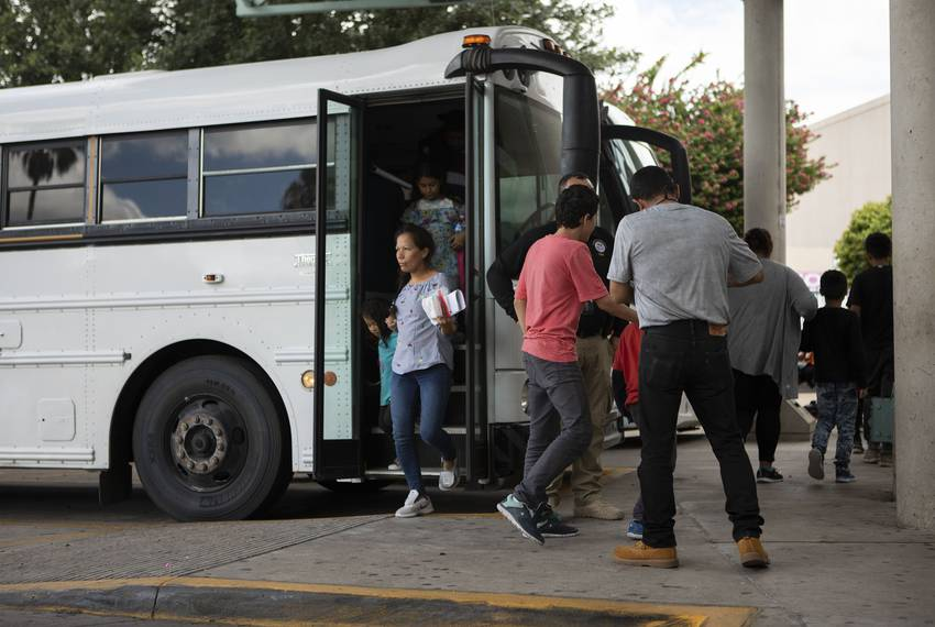 A group of migrants exit an immigration bus at the McAllen Central Station in downtown McAllen on June 25, 2019.