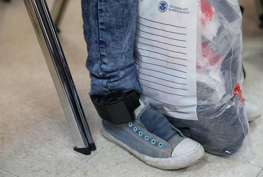 After being detained and released by law enforcement, an undocumented immigrant wears an ankle monitor at the Catholic Cha...
