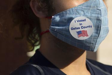"""A voter has an """"I Voted in Dallas County"""" sticker at the Oak Lawn Branch Library polling location in Dallas during the state primary runoff election on July 14, 2020."""