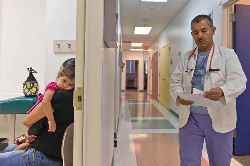 Yesenia Alvarado holds her daughter, Medicaid patient Melanie Almaraz, 2, while waiting to see Dr. Alberto Vasquez for treatment of a fever at the Su Clinica Familiar in Harlingen, Texas on Jul. 9, 2013.