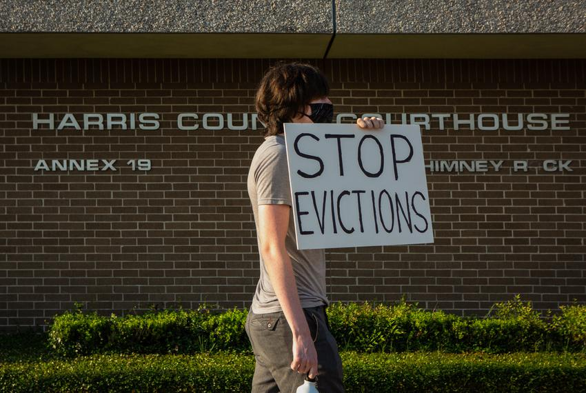"A protester holds up a ""stop evictions"" sign outside the Harris County Courthouse in Houston on Aug. 21, 2020."