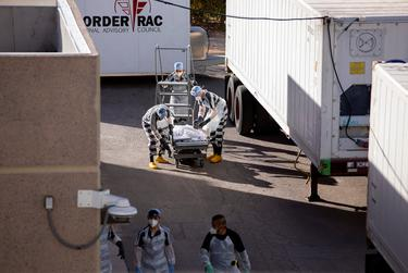 """El Paso County detention inmates, also known as """"trustees"""" who are low-level offenders, help move bodies to mobile morgue units outside the Medical Examiner's Office in El Paso on Nov. 14, 2020."""