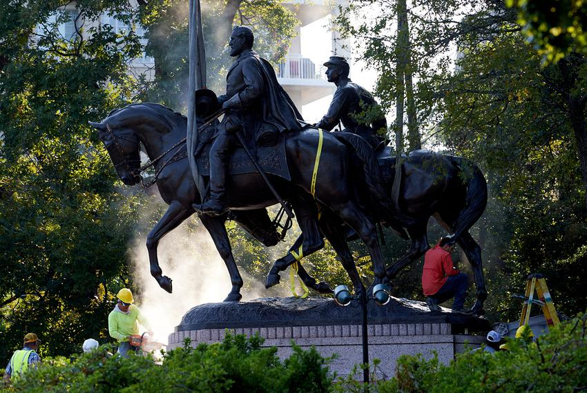 A statue of Robert E. Lee is harnessed to a crane as workers cut it from its base at Lee Park in Dallas on Sept. 14, 2017.