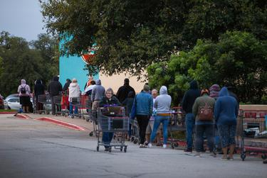 Shoppers lined up outside H-E-B before it opened one day in March. The COVID-19 outbreak caused the grocery chain to shorten its store hours in order to restock its inventory.