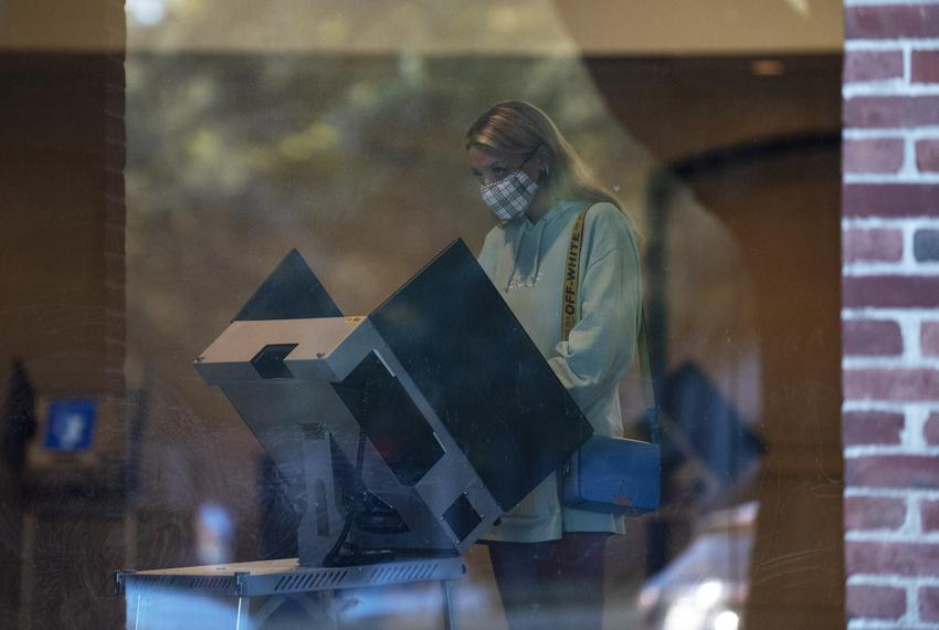 A young women wearing a face covering votes inside the polling location at University Park United Methodist Church in Dallas…