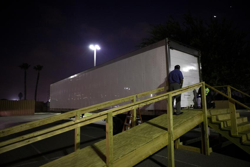 Juan Lopez waits to pick up a body from a refrigerated trailer at Doctors Health at Renaissance