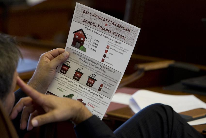 A lawmaker reads a flyer with property tax information that was distributed to Texas House members' desks on Aug. 12, 2017.