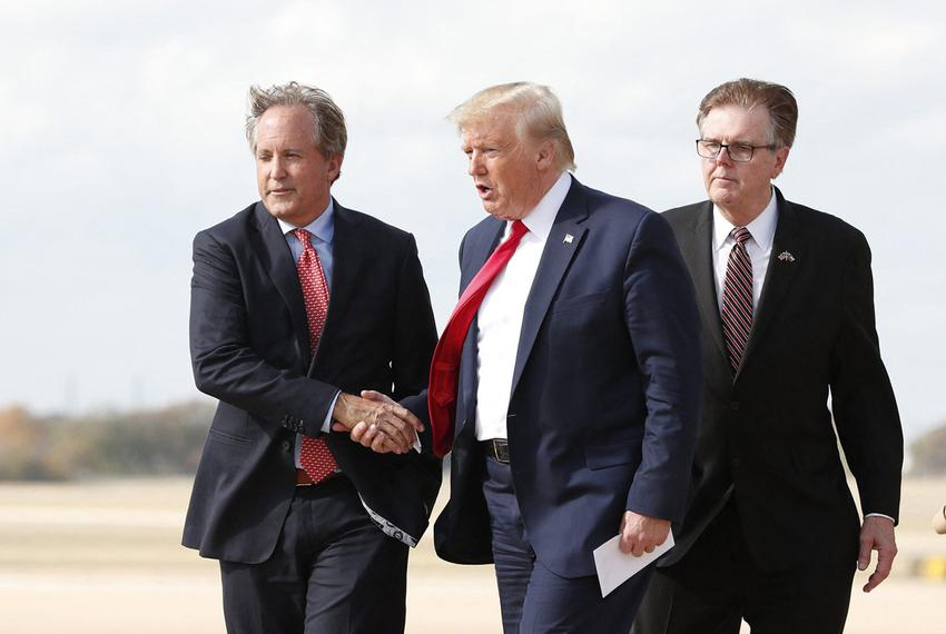 Attorney General Ken Paxton greets President Donald Trump as Lt. Gov. Dan Patrick follows at Austin Bergstrom International …